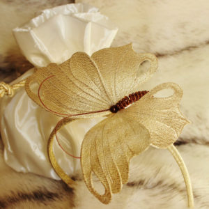 Golden fascinator with a butterfly