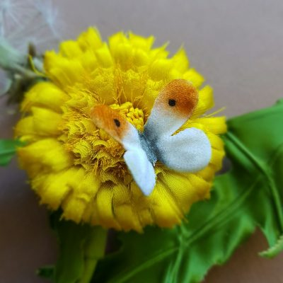silk dandelion flower and clock corsage closeup